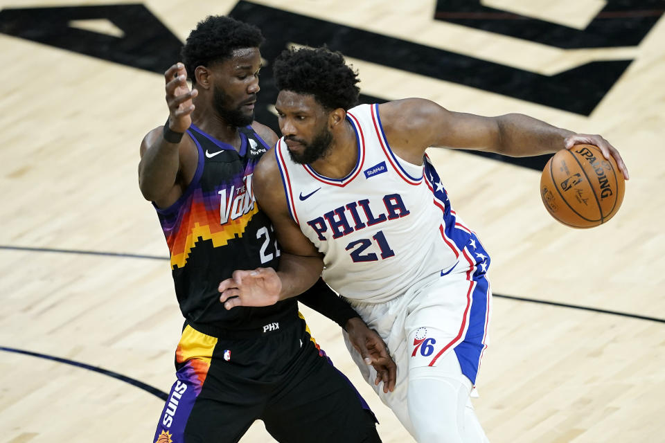 Philadelphia 76ers center Joel Embiid (21) drives on Phoenix Suns center Deandre Ayton during the first half of an NBA basketball game, Saturday, Feb. 13, 2021, in Phoenix.(AP Photo/Matt York)