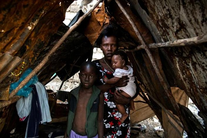 Etienne, 10, Jolande Baptiste, 27, and Lenia Cha, 4 months, pose inside a makeshift shelter on the site of their home which was burned during a November 2018 gang war in Port-au-Prince (AFP Photo/CHANDAN KHANNA)