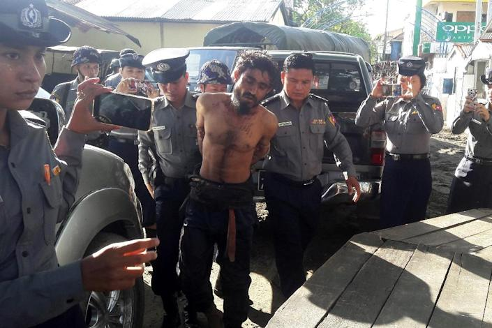 A man suspected of being one of the attackers in recent border raids is taken to a police station in Sittwe, capital of the Rakhine state on October 9, 2016 (AFP Photo/)