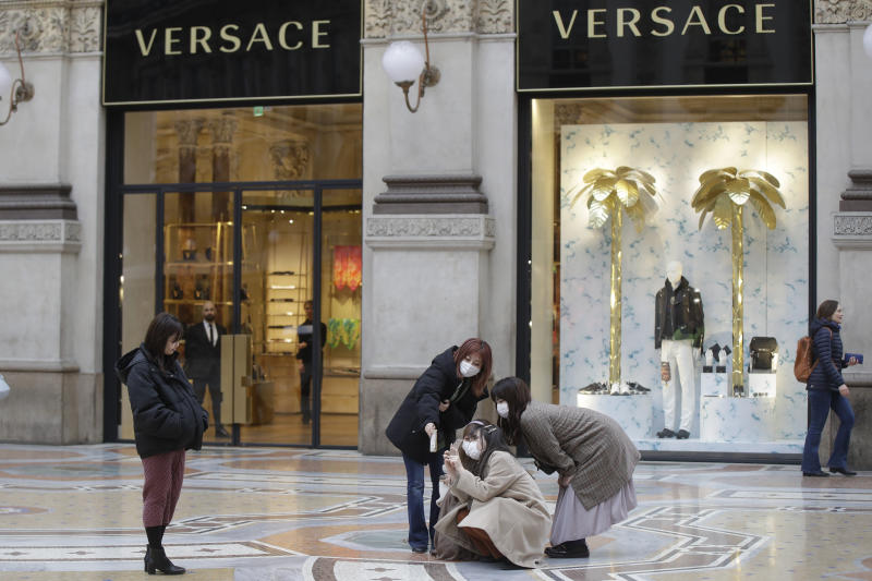 Tourists, wearing face masks, pose for a selfie in front of a Versace shop window in downtown Milan, Italy, Thursday, Feb. 27, 2020. In Europe, an expanding cluster in northern Italy is eyed as a source for transmissions. (AP Photo/Luca Bruno)