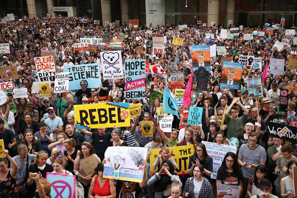 Large crowd at a climate change protest hold up signs.