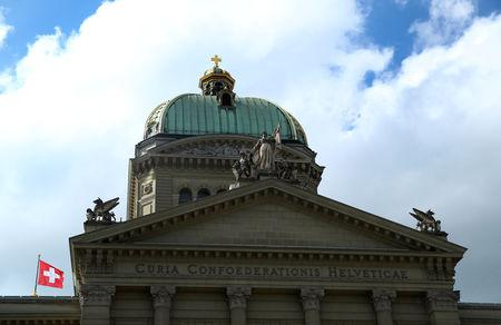 Swiss flags are pictured on the Swiss Federal Palace (Bundeshaus) on a windy spring day in Bern