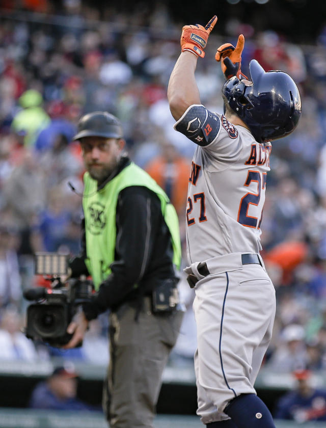 Houston Astros' Jose Altuve (27) points skyward after hitting a two-run home run during the first inning of the team's baseball game against the Texas Rangers, Friday, April 19, 2019, in Arlington, Texas. (AP Photo/Brandon Wade)