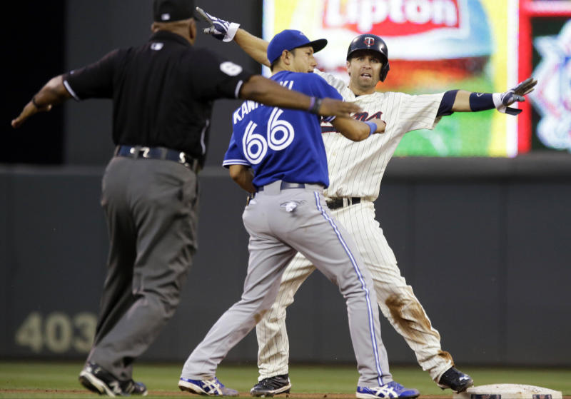 Minnesota Twins' Brian Dozier, right, signals that he is safe after Toronto Blue Jays second baseman Munenori had to go high for an errant throw from third baseman Brett Lawrie during the fourth inning of a baseball game, Saturday, Sept. 7, 2013, in Minneapolis. (AP Photo/Jim Mone)