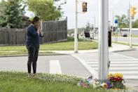 A woman pays her respects at the scene where a man driving a pickup truck struck and killed four members of a Muslim family in London, Ontario, Canada