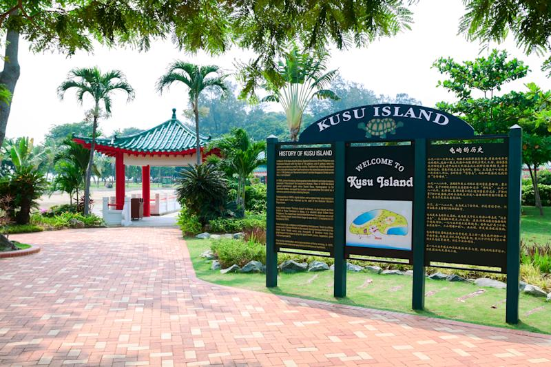 """""""Singapore, Singapore - September, 24th 2012: Welcome board and information board on Kusu Island, small island in South of Singapore. On island are two temples, places of yearly pilgrimage. Kusu Island is one of several small islands belonging to Singapore. In background is entrance to Buddhist temple."""""""