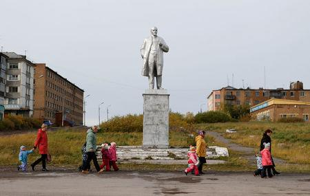 Pupils of a local nursery school and adults walk past a monument to Soviet state founder Vladimir Lenin in Vorgashor settlement outside the far northern city of Vorkuta