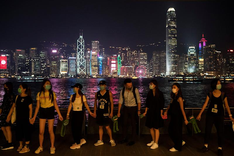 People form a human chain in support of protest movement in the harbor area in Hong Kong, Monday, Sept. 30, 2019.