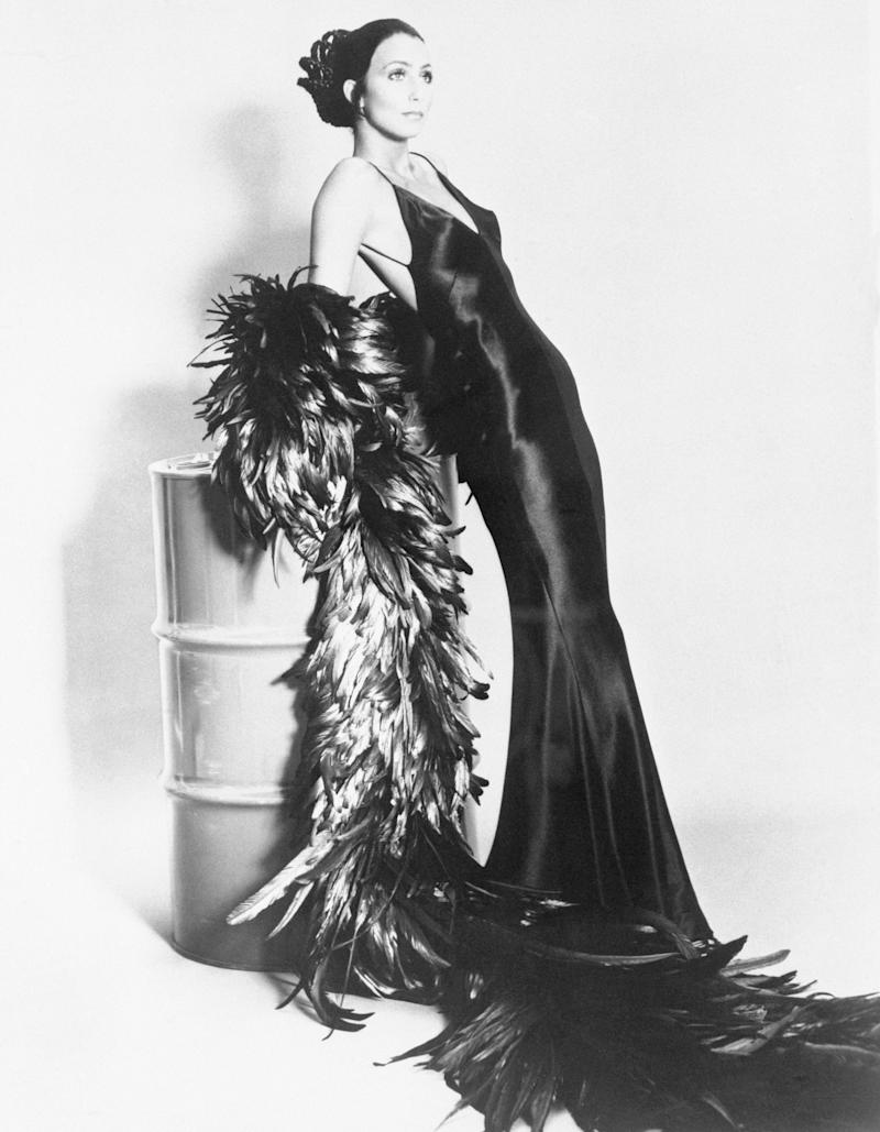 Singer Cher Bono, modeling elegant gowns and outfits. Photo shows Cher modeling a sleek black gown leaning on a white tin, with a long black boa.