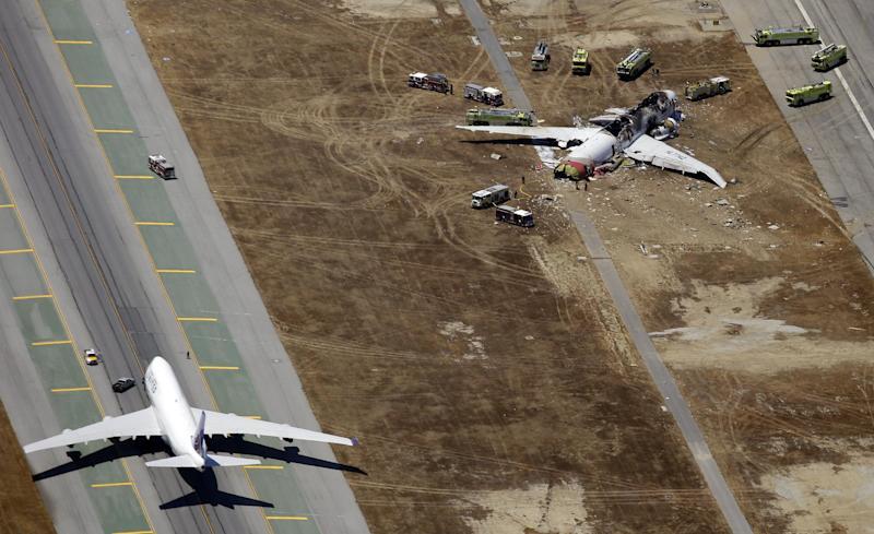 In this Saturday, July 6, 2013 aerial photo, emergency crews respond at the scene of the wreckage of Asiana Flight 214, top right, after it crashed at the San Francisco International Airport in San Francisco, earlier in the day. The pilot at the controls of airliner had just 43 hours of flight time in the Boeing 777 and was landing one for the first time at San Francisco International. (AP Photo/Marcio Jose Sanchez)