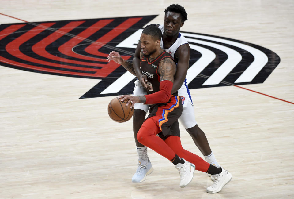 Portland Trail Blazers guard Damian Lillard, left, is fouled by Detroit Pistons forward Sekou Doumbouya during the first half of an NBA basketball game in Portland, Ore., Saturday, April 10, 2021. (AP Photo/Steve Dykes)