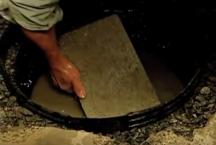 Hand places flat stone in basin.