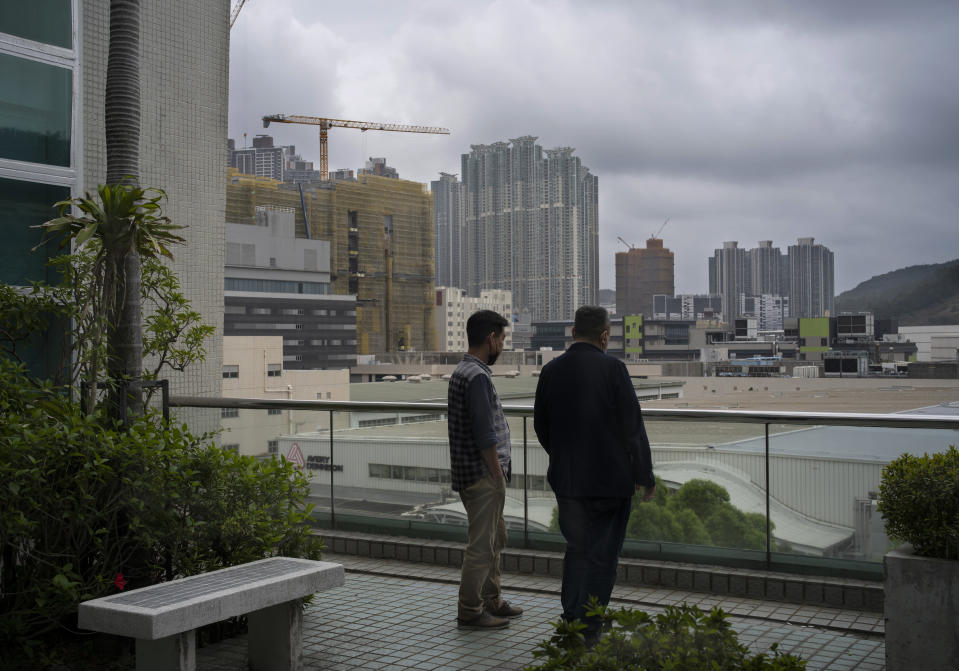Two senior editors take rest at the terrace outside the news room of Apple Daily, Monday, April 26, 2021, in Hong Kong. A newspaper that has advocated for greater democracy in Hong Kong came under further pressure this week with the arrests of three top editors and two senior executives. (AP Photo/Vincent Yu)
