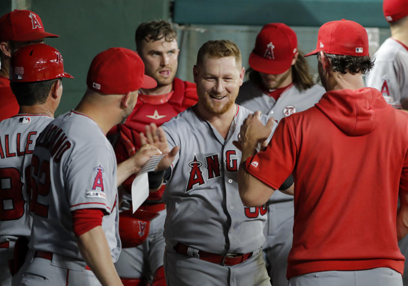 Los Angeles Angels' Kole Calhoun, center, is congratulated in the dugout after making an over-the-shoulder catch on a Texas Rangers' Elvis Andrus flyout to end to bottom of the fourth inning of baseball game in Arlington, Texas, Monday, Aug. 19, 2019. (AP Photo/Tony Gutierrez)