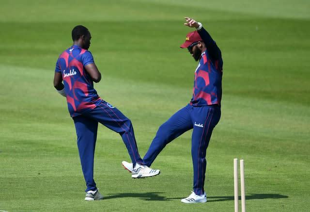 Marquino Mindley, left, celebrates the wicket of Jermaine Blackwood with John Campbell (Gareth Copley/PA)