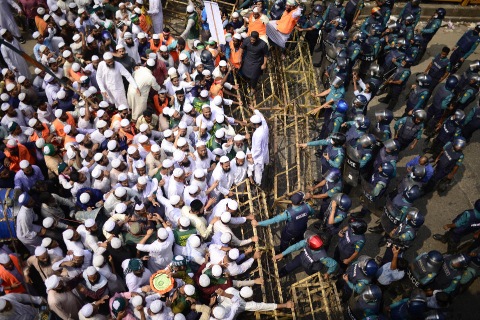 Supporters of Islami Andolan Bangladesh, an Islamist political party, face a barrier during a protest against French President Emmanuel Macron and against the publishing of caricatures of the Prophet Muhammad they deem blasphemous, in Dhaka, Bangladesh, Tuesday, Oct. 27, 2020. Muslims in the Middle East and beyond on Monday called for boycotts of French products and for protests over the caricatures, but Macron has vowed his country will not back down from its secular ideals and defense of free speech. (AP Photo/Mahmud Hossain Opu)