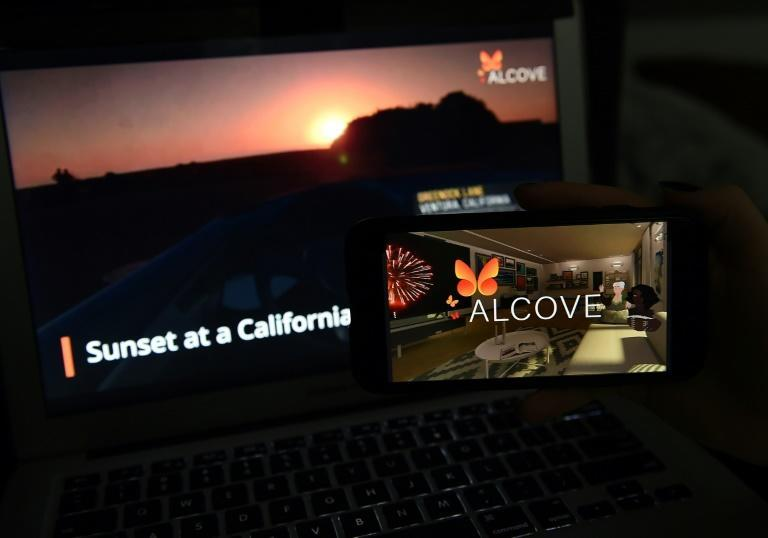 This illustration picture shows a virtual road trip on a computer and the travel application logo from Alcove VR displayed on a smartphone
