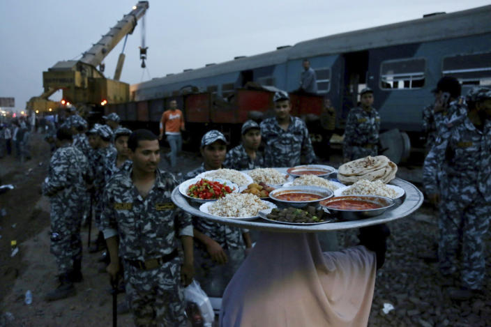 A woman brings food for security forces to break their fast during the holy month of Ramadan, at the site of a passenger train that derailed injuring about 100 people, near Banha, Qalyubia province, Egypt, Sunday, April 18, 2021. At least eight train wagons ran off the railway, the provincial governor's office said in a statement. (AP Photo/Fadel Dawood)