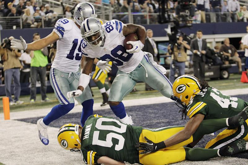 Dallas Cowboys wide receiver Dez Bryant (88) pulls in a touchdown pass over Green Bay Packers inside linebacker A.J. Hawk (50) and free safety M.D. Jennings (43) as Cowboys' wide receiver Miles Austin (19) looks on during the second half of an NFL football game, Sunday, Dec. 15, 2013, in Arlington, Texas. (AP Photo/Tim Sharp)