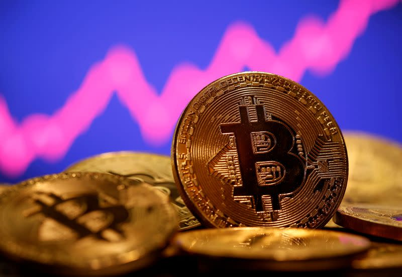 FILE PHOTO: FILE PHOTO: A representation of virtual currency Bitcoin is seen in front of a stock graph in this illustration taken
