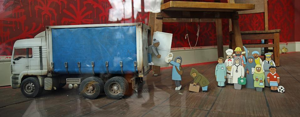 A toddler's counting toy, where children are encouraged to load wooden migrant figures inside a haulage truck, that is amongst the merchandise in Gross Domestic Product, a homeware store that is being launched in South London by the graffiti artist Banksy.