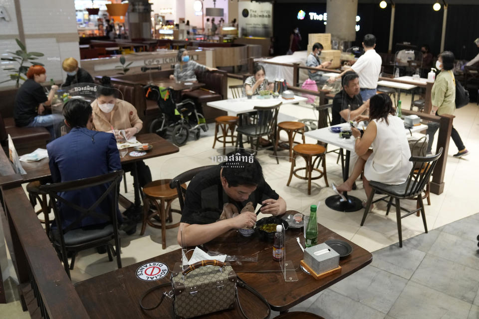 A man, front, eats a meal during the opening at the Paragon shopping mall in Bangkok, Thailand, Wednesday, Sept. 1, 2021. Thailand to ease business lockdown measures in the capital and provinces where restrictions have been implemented since mid-July. Malls, hair salons, foot massage parlors, and parks will be allowed to re-open, as well as restaurants for dine-in services but maintained at 50% capacity. (AP Photo/Sakchai Lalit)