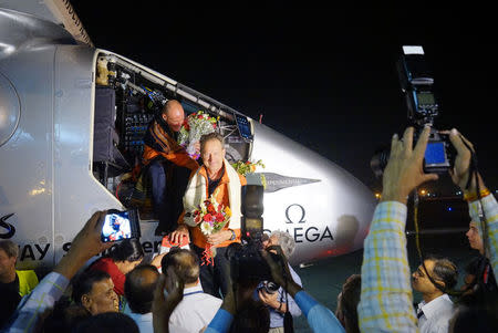 Pilot Bertrand Piccard (L) and pilot Andre Boschberg are welcomed after landing Solar Impulse 2, the world's first airplane flying on solar energy, in Ahmedabad March 10, 2015. REUTERS/Jean Revillard/Handout via Reuters
