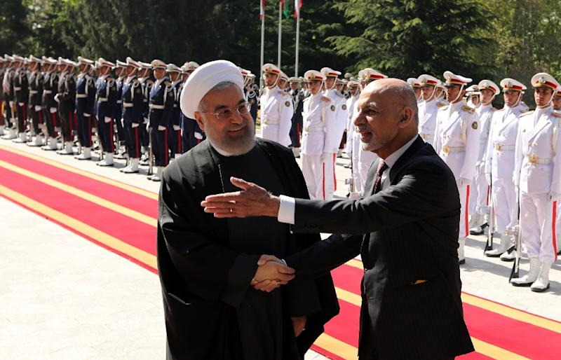 Iran's President Hassan Rouhani shakes hands with Afghan President Mohammad Ashraf Ghani (R) during an official welcoming ceremony following the latter's arrival at the Saadabad Palace in Tehran on April 19, 2015 (AFP Photo/Atta Kenare)