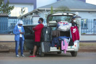 People sell clothes displayed on their car by the side of a busy road in Harare, Zimbabwe, Tuesday, June, 23, 2020. Cars have become mobile markets in Zimbabwe where enterprising residents are selling goods from their vehicles to cope with economic hardships caused by the coronavirus. With their car doors and trunks wide open by the side of busy roads, eager sellers display a colorful array of goods in Harare, the capital. (AP Photo/Tsvangirayi Mukwazhi)