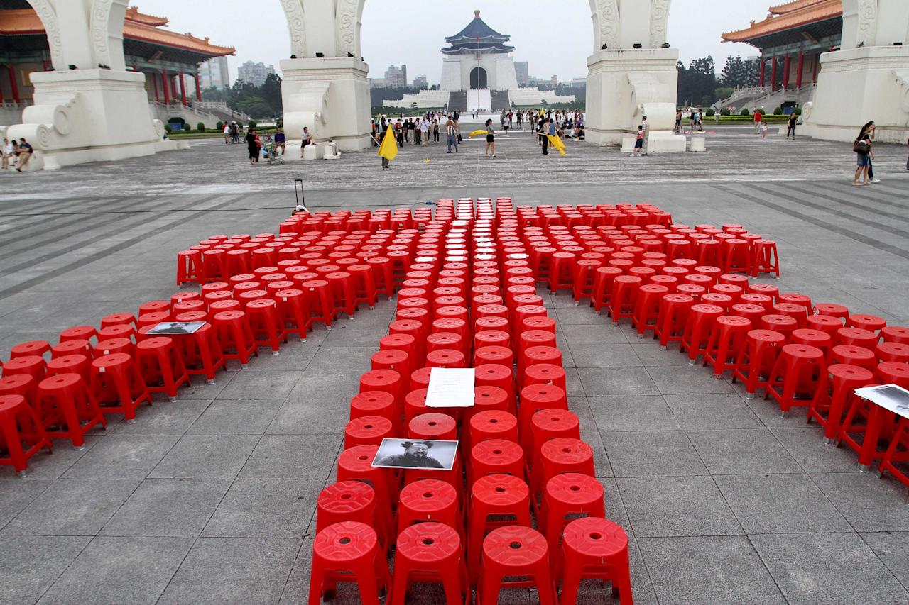 "Hundreds of red plastic chairs are arranged to form one of Chinese characters of Chinese artist and activist Ai Weiwei's name to support him on the Liberty Square in front of the Chiang Kai-shek Memorial Hall in Taipei, Taiwan, Saturday, June 4, 2011. Chinese police detained Ai on April 3, 2011 without laying any official charges and the authorities alleged a company controlled by Ai evaded ""huge amount"" of tax."