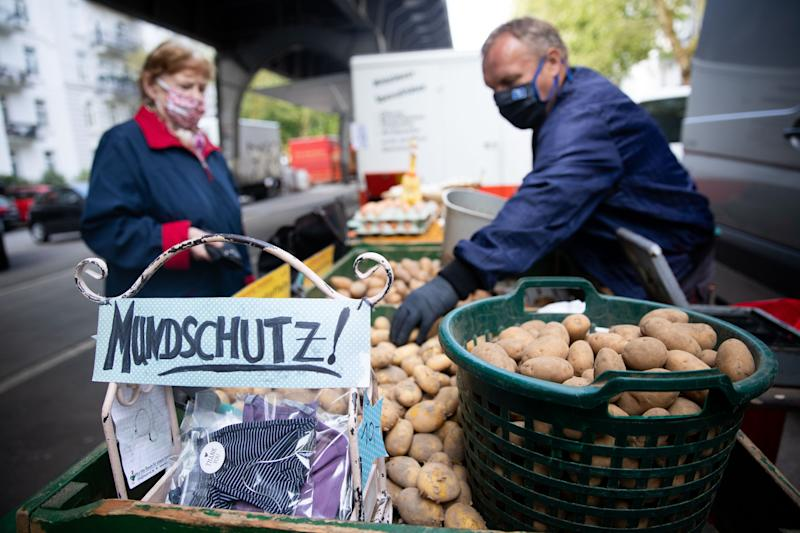 28 April 2020, Hamburg: A market trader at Isemarkt offers not only his potatoes and eggs but also the handmade mouthguard of a colleague. Photo: Christian Charisius/dpa (Photo by Christian Charisius/picture alliance via Getty Images)