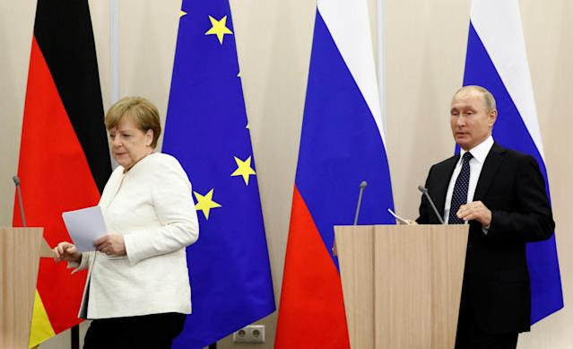 Russian President Vladimir Putin and German Chancellor Angela Merkel arrive for a joint news conference following their meeting in the Black Sea resort of Sochi, Russia May 18, 2018. REUTERS/Sergei Karpukhin