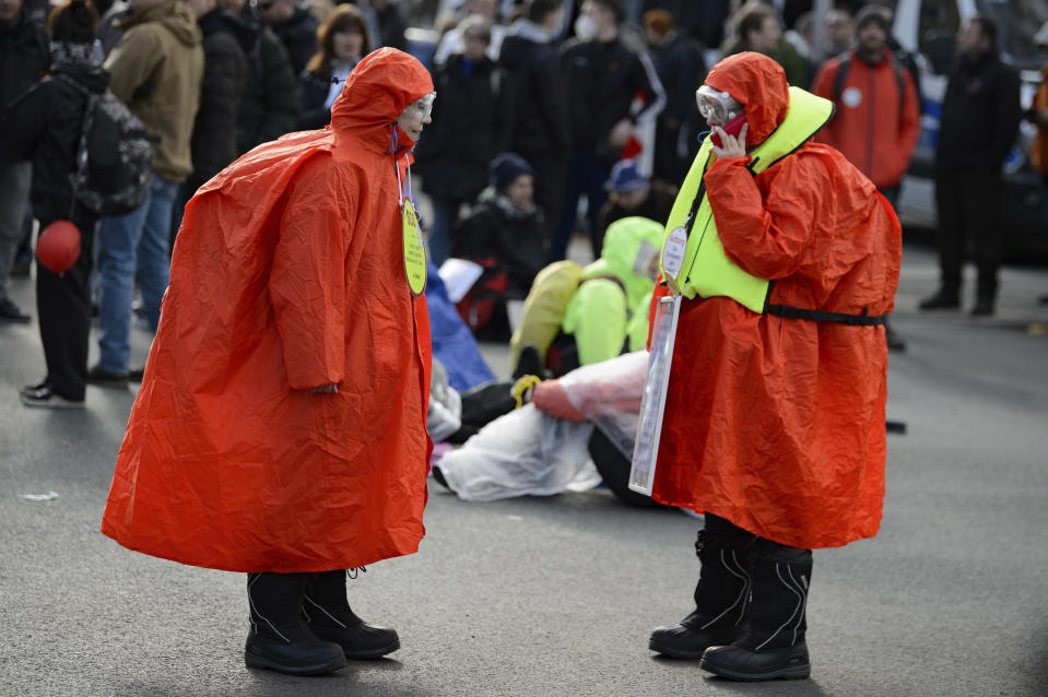 "Participants wearing red coats stand in the street during a rally under the slogan ""Free Citizens Kassel - Basic Rights and Democracy"" in Kassel, Germany, Saturday, March 20, 2021. (Swen Pfoertner/dpa via AP)"