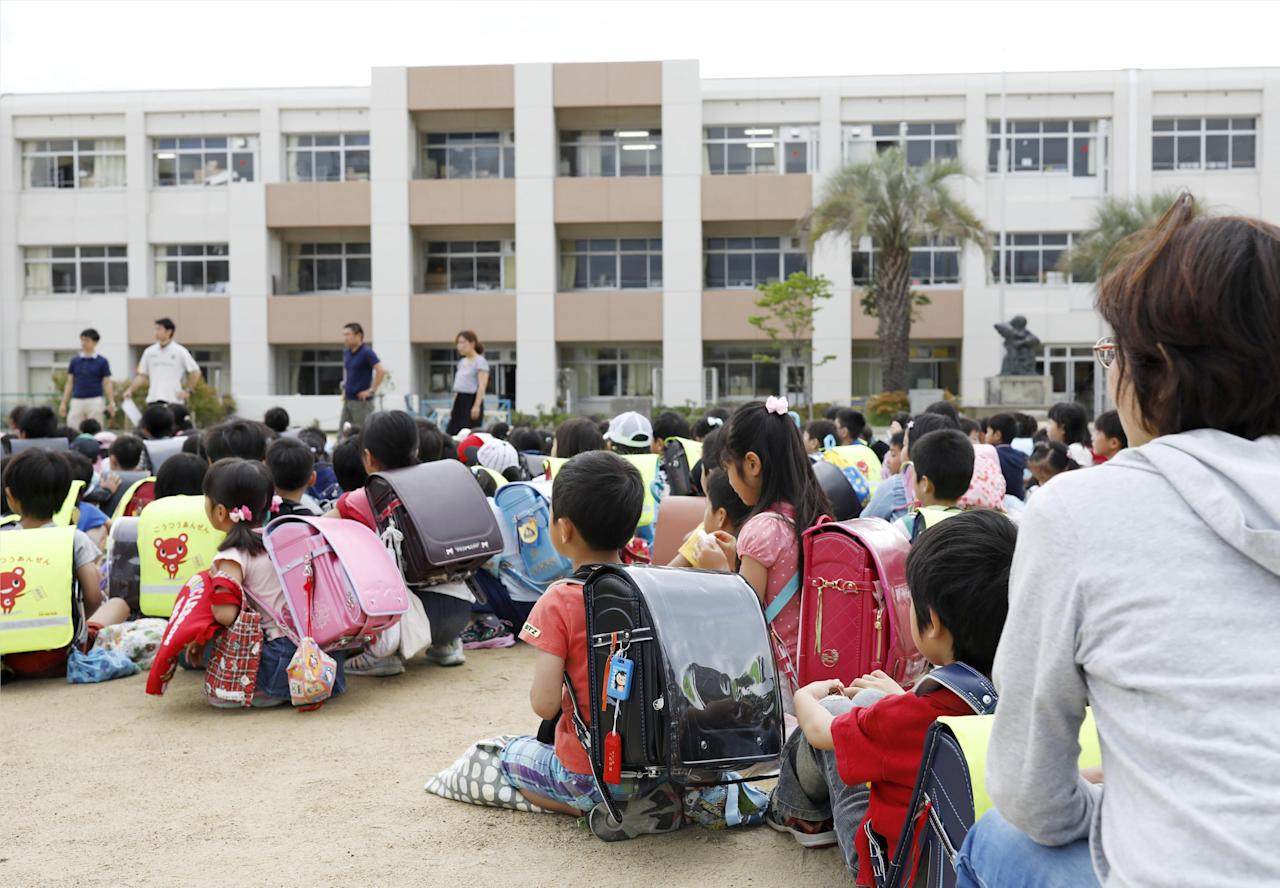 Students sit on a playground after they were evacuated from school building after an earthquake at Ikeda elementary school in Ikeda, Osaka prefecture, western Japan, in this photo taken by Kyodo June 18, 2018.   Mandatory credit Kyodo/via REUTERS ATTENTION EDITORS - THIS IMAGE WAS PROVIDED BY A THIRD PARTY. MANDATORY CREDIT. JAPAN OUT. NO COMMERCIAL OR EDITORIAL SALES IN JAPAN.