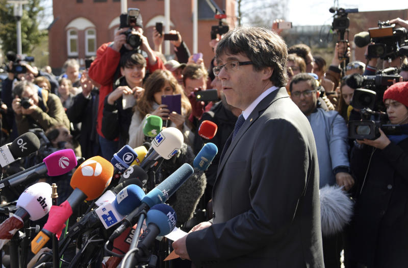 Former Catalan leader Carles Puigdemont gives a press statement after he was released on bail from the prison in Neumuenster, northern Germany, Friday, April 6, 2018. (Axel Heimken/dpa via AP)