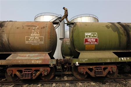 A worker walks atop a tanker wagon to check the freight level at an oil terminal on outskirts of Kolkata