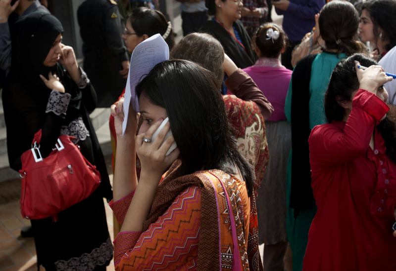 People evacuate buildings and call their relatives after a tremor of an earthquake was felt in Karachi, Pakistan, Tuesday, April 16, 2013. A major earthquake described as the strongest to hit Iran in more than half a century flatted homes and offices Tuesday near Iran's border with Pakistan, killing at least tens of people in the sparsely populated region and swaying buildings as far away as New Delhi and the skyscrapers in Dubai and Bahrain. (AP Photo/Shakil Adil)