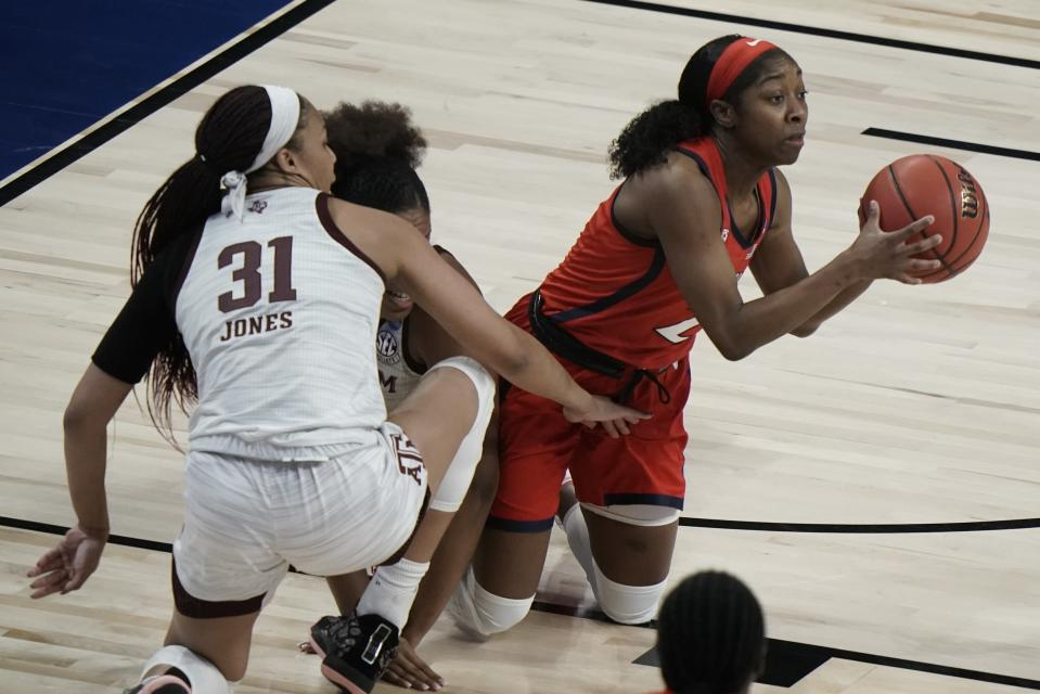 Arizona's Aari McDonald looks to pass from her knees with Texas A&M's N'dea Jones defending during the the first half of an NCAA college basketball game in the Sweet 16 round of the Women's NCAA tournament Saturday, March 27, 2021, at the Alamodome in San Antonio. (AP Photo/Morry Gash)