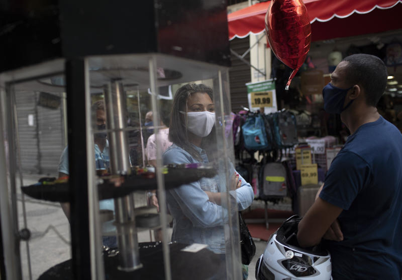 People wearing masks to prevent the spread of the new coronavirus line up to get their temperature checked before entering a store in downtown Rio de Janeiro, Brazil, Monday, June 29, 2020. This weekend Rio authorities allowed commerce and beauty salons to open their doors to the public as the city eases its lockdown amid the growing pandemic. (AP Photo/Silvia Izquierdo)