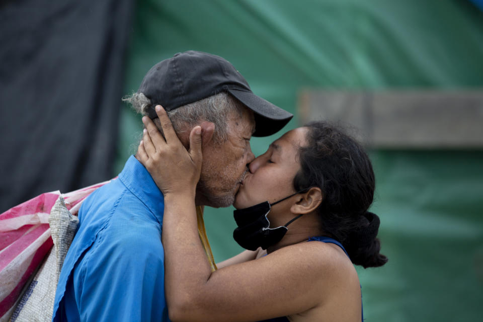 A couple kiss at the shelter where they live since losing their home in last year's hurricanes Eta and Iota, in La Lima, on the outskirts of San Pedro Sula, Honduras, Monday, Jan. 11, 2021. The devastation wrought by November's hurricanes and the economic damage of the COVID-19 pandemic has added to the forces of poverty and gang violence that drive Hondurans to migrate. (AP Photo/Moises Castillo)