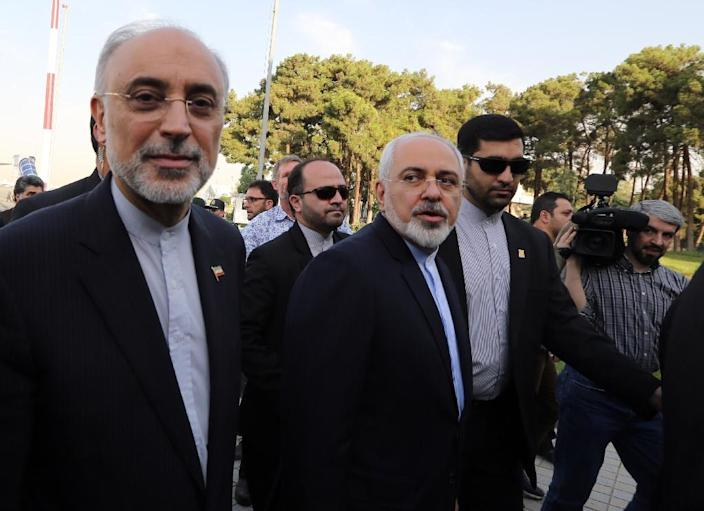Iranian Foreign Minister Mohammad Javad Zarif (C) and the head of Iran's Atomic Energy Organization Ali Akbar Salehi (L) arrive at Tehran's Mehrabad Airport on July 15, 2015, after striking a deal with world powers in Vienna (AFP Photo/Atta Kenare)