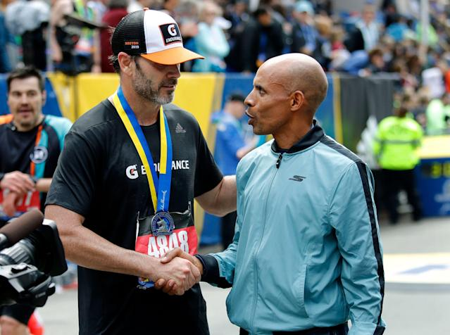 NASCAR star Jimmie Johnson, left, completed the Boston Marathon on Monday and received his medal from race marshal and 2014 champion Meb Keflezighi. (AP)