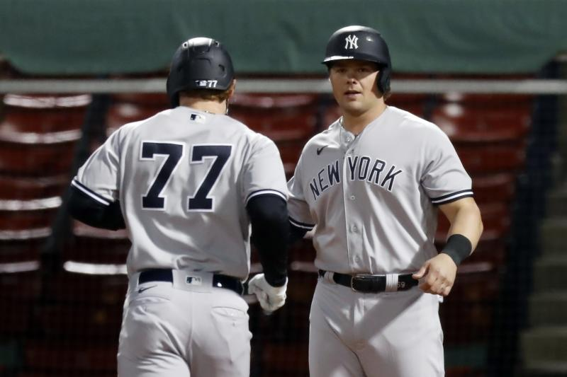 New York Yankees' Clint Frazier (77) crosses home plate on his two-run home run that also drove in Luke Voit, right, during the fifth inning of a baseball game against the Boston Red Sox, Saturday, Sept. 19, 2020, in Boston. (AP Photo/Michael Dwyer)