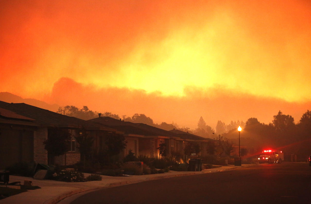 <p>Fire trucks monitor a fire that threatens the Oakmont community along Highway 12 in Santa Rosa on Oct. 13, 2017. The retirement community had been evacuated on the second day of the Santa Rosa fire. (Photo : Genaro Molina/Los Angeles Times via Getty Images) </p>