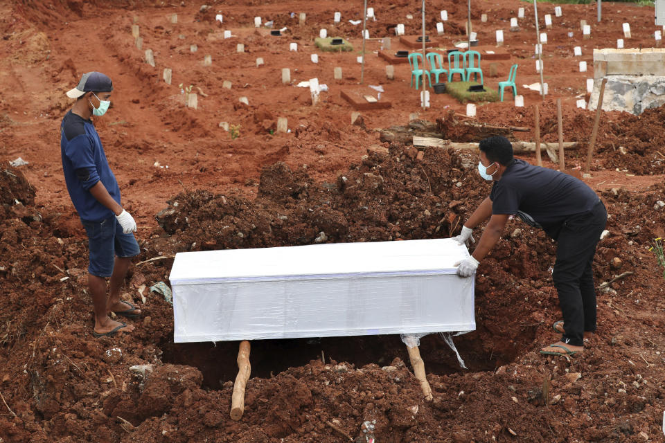 Workers prepare a coffin for burial at the special section of Jombang cemetery which was opened to accommodate the surge in deaths during coronavirus outbreak, in Tangerang, Indonesia, Tuesday, Jan. 26, 2021. Indonesia has reported more cases of the virus than any other countries in Southeast Asia. (AP Photo/Tatan Syuflana)
