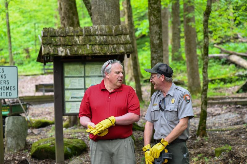 This Wednesday, May 6, 2020 image from a tweet by Interior Secretary David Bernhardt, the Interior Secretary visits with National Parks Service employees at Great Smoky Mountains National Park. While the Interior Secretary asked visitors to social distance when the park reopens on May 9, neither Bernhardt nor park staff wore face masks in the photos, as they talked and walked inches apart during his visit on Tuesday, May 5.  (National Parks Service via AP)
