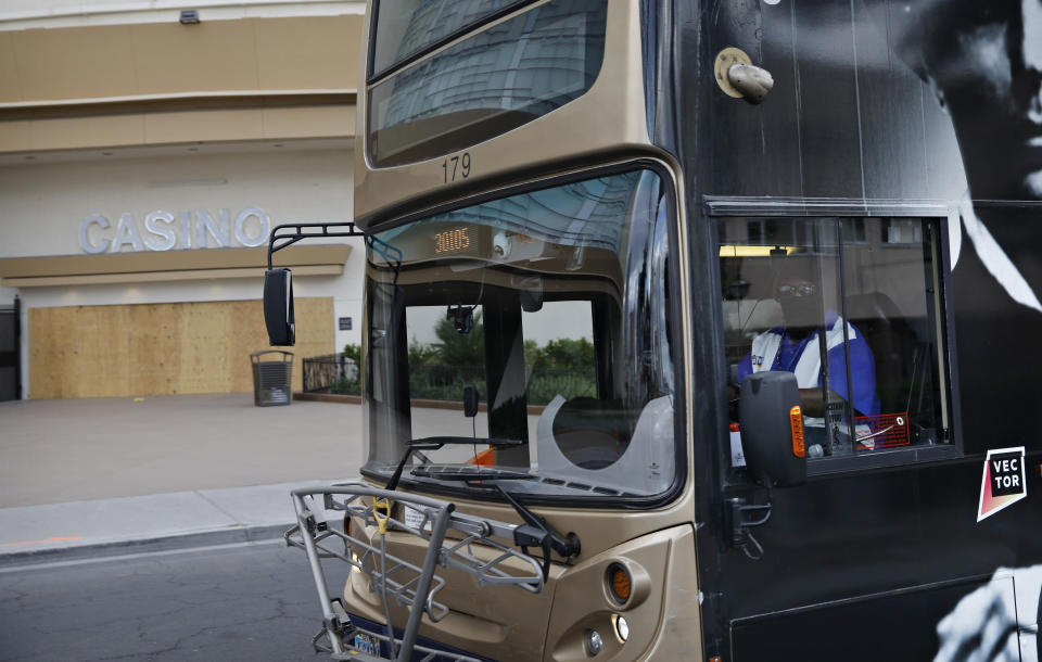 In this April 21, 2020, photo, a bus driver in a mask drives by a boarded-up casino along the Strip in Las Vegas. Bus service in parts of the city has been reduced during the coronavirus shutdown. (AP Photo/John Locher)