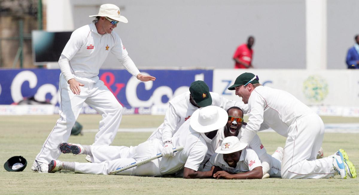 Zimabwe players celebrate victory on September 14, 2013 during the fifth day of the second Test against Pakistan at the Harare Sports Club.                              AFP PHOTO / JEKESAI NJIKIZANA        (Photo credit should read JEKESAI NJIKIZANA/AFP/Getty Images)