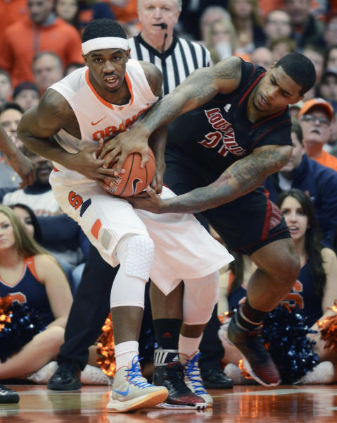 Syracuse's C. J. Fair, left, battles Louisville's Chane Behanan for a loose ball during the first half of an NCAA college basketball game in Syracuse, N.Y., Saturday, March 2, 2013. (AP Photo/Kevin Rivoli)