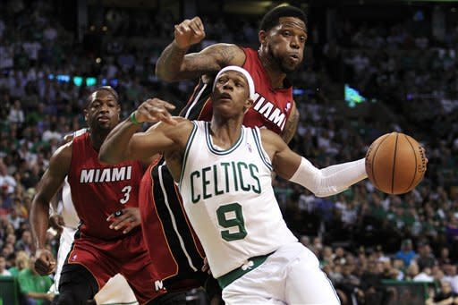 Boston Celtics guard Rajon Rondo (9) drives against Miami Heat forward Udonis Haslem (40) while guard Dwyane Wade (3) watches during the first quarter of Game 6 of the NBA basketball Eastern Conference finals, Thursday, June 7, 2012, in Boston. (AP Photo/Elise Amendola)